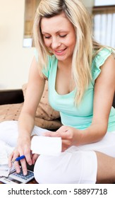 Bright young woman using her calculator holding a bill in the living room