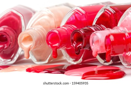 Bright-colored nail polish spilling from bottles