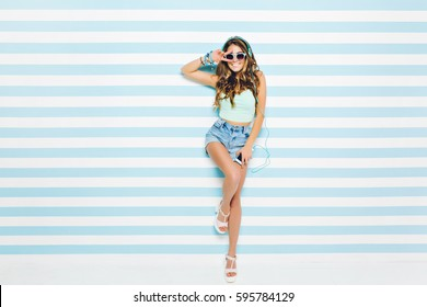 Brightful summer look of joyful young woman with long curly hair, in sunglasses, shorts on heels having fun on striped background. Blue colors, expressing positivity, music, joy, happiness