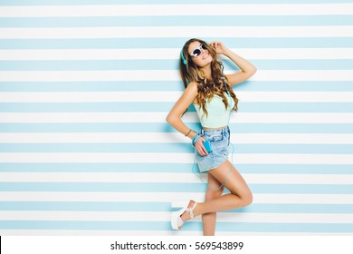 Brightful summer time of attractive joyful young woman in denim shorts listening to music through blue headphones on striped background. Pastel, blue colors, expressing positive emotions, having fun