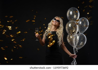 Brightfull expressions of happy emotions of  amazing blonde girl celebrating party on black background. Luxury black dresses, smiling, a glass of champagne, golden tinsels,  balloons, long curly hair