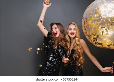 Brightfull expressions of happy emotions of two amazing girls celebrating party on black background. Luxury black dresses, smiling, golden tinsels, big balloon, long curly hair, stylish look