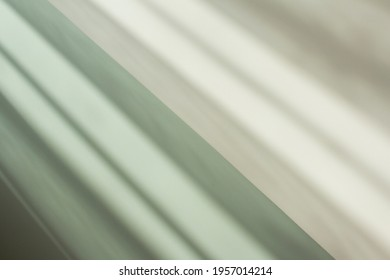 Bright,iridescent and fresh color palette mixing by gradient from light green with gray. Conceptual creative abstract background with diagonal layers and natural shadows from the window for templates.
