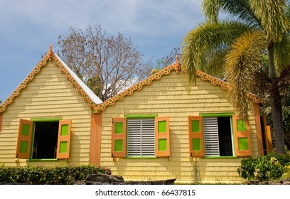 Brightly colored buildings in the tropics under a palm tree