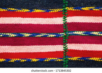 Brightly colored Bulgarian woven handmade woollen rug texture with a red and white stripes decorated with blue, yellow and green patterns in a fill frame detailed view