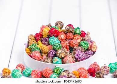 Brightly Colored Candied Popcorn, white background. Horizontal image of Junk food, fruit flavored popcorn in light pink bowl. Colorful, rainbow, candy coated popcorn. Shallow focus on popcorn in bowl