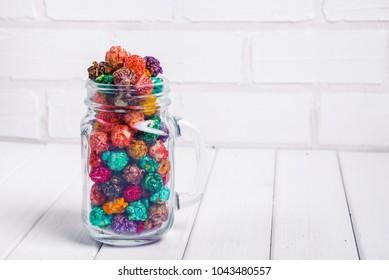 Brightly Colored Candied Popcorn, white background. Horizontal image of Junk food, fruit flavored popcorn in glass jar mason. Colorful, rainbow, candy coated popcorn. On the wooden table, selective
