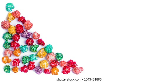 Brightly Colored Candied Popcorn, white background. Horizontal image of Junk food, fruit flavored popcorn in light pink bowl. Colorful, rainbow, candy coated popcorn. Shallow focus  Isolated on white.