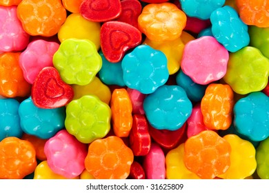 brightly colored candy pieces set on  white background, and shot with high key lighting