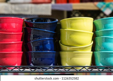Brightly colored ceramic bowls are stacked on a shelf for sale at an antique festival.