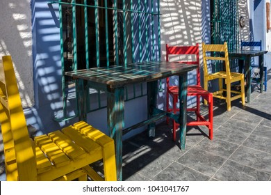 Brightly Colored Chairs Line the Sidewalk Outside of a Local Restaraunt in Todos Santos, Mexico on a Sunny Day