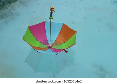 Brightly colored children's umbrella floating on blue pool with shadow