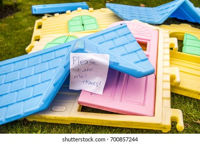 A brightly colored child's playhouse lays disassembled on the ground with a sign reading 'please take me , thanks'