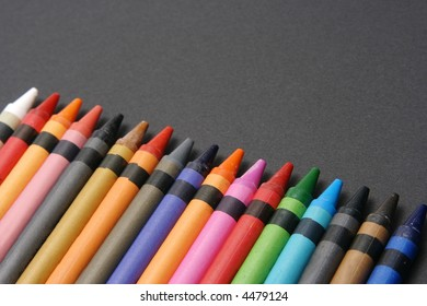 Brightly colored crayons lined up on black paper.