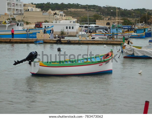 Brightly Colored Fishing Boats at Malta with people taking pictures in background