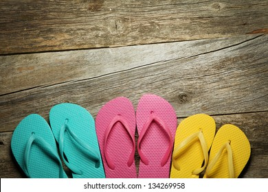 Brightly colored flip-flops on wood. Family vacation