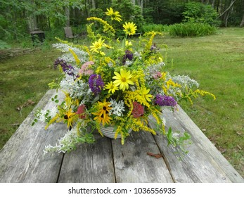 Brightly colored flowers in a basket on top of a rustic picnic table with a woodland background