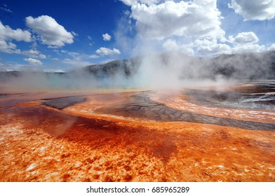 Brightly colored geothermal steam vent at Yellowstone National Park against bright blue skies with white clouds.