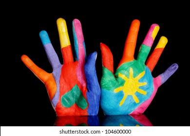 Brightly colored hands on black background close-up