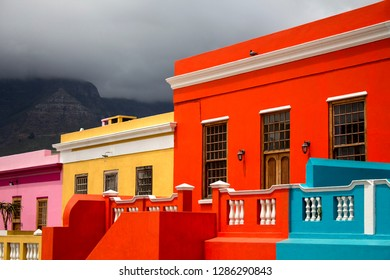 The brightly colored houses of Bo-Kaap, Cape Town. South Africa. The stunning view of Signal Hill from Bo-Kaap, the Cape Malay Quarter. The famous tourist attraction. British style colorful buildings.