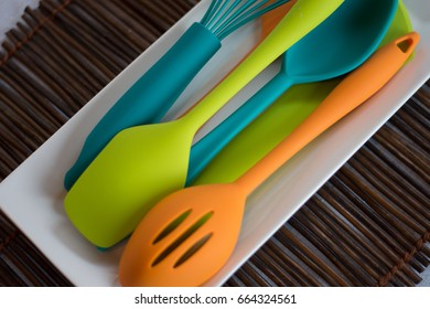 Brightly colored kitchen utensils on a modern white plate