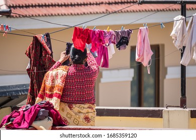 Brightly colored laundry being hung on a line by a South Asian woman