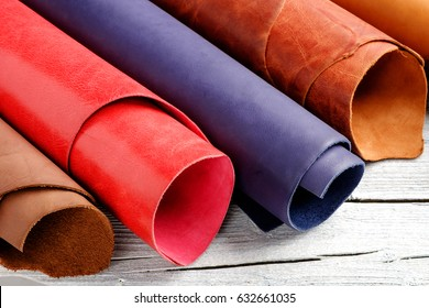 Brightly colored leather in rolls on the white wooden background. Leather craft.