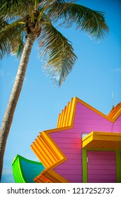 Brightly colored lifeguard towers standing under tall palm trees in South Beach, Miami, Florida, USA