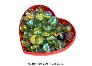 Brightly colored marbles in a heart shaped box with a white background