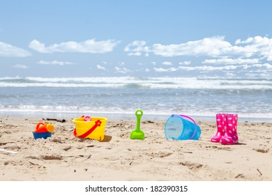 Brightly colored plastic beach toys on the beach with the ocean and clouds in background