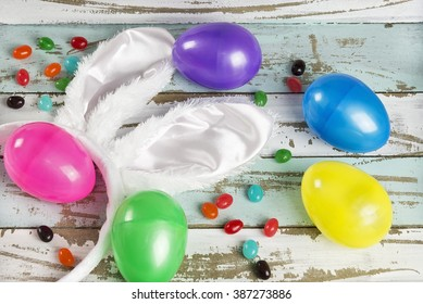 Brightly colored plastic Easter eggs, jelly beans and a pair of white Easter bunny ears form an Easter still life on a weathered rustic background.