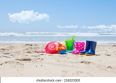 Brightly colored plastic toys and gumboots on the beach sand