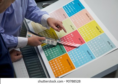 A brightly colored printed calendar being checked by a business man and a printing machine minder