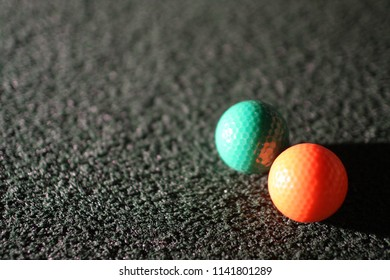 Brightly colored putt-putt balls at rest.