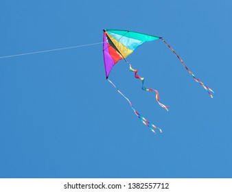 Brightly colored rainbow kite against blue sky.