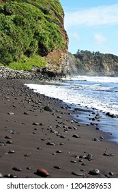 Brightly colored rocks strewn along a black sand beach ending in a cliffside and meeting the Pacific Ocean in the Pololu Valley in North Kohala, Hawaii