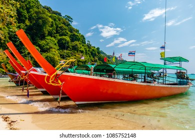 Brightly colored traditional longtail boats moored on a beautiful tropical sandy beach