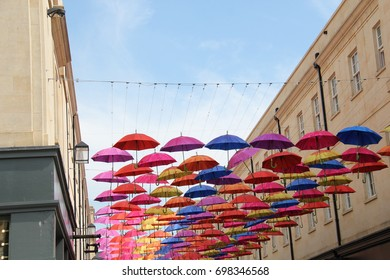 brightly colored umbrellas hanging across a shopping street under a blue sky