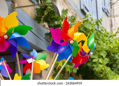 Brightly colored wind toys against an old wall with a grape vine.