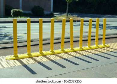 Brightly colored yellow bollard style barrier along commuter rail line consisting of ten vertical flexible posts