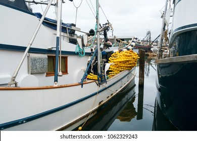 Brightly colored yellow net floats on sleek white and blue fishing boat on calm morning at Fishermen's Terminal in Seattle, Washington