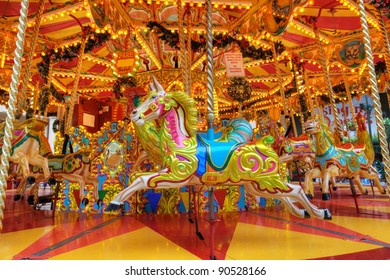 Brightly coloured carousel with galloping ponies.