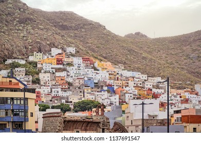 A brightly coloured traditional fishing village set into a mountainside with a ruined castle for fighting pirates in the foreground. San Andrés, Tenerife, is one of the Canary Island's oldest villages