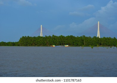 A brightly coloured transport ship is luminescent in the aftenoon light. It is beside a forest on the Mekong Delta. Behind rise the poles of a large bridge. The sky is blue with some clouds.