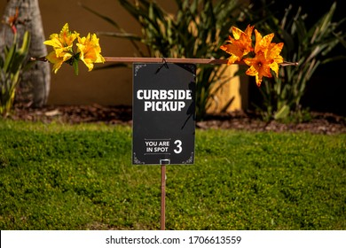 Brightly decorated curbside pick up sign at restaurant