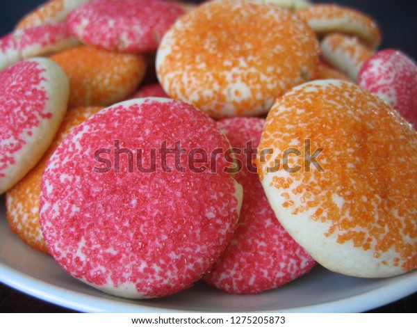 Brightly decorated homemade sugar cookies in orange and red