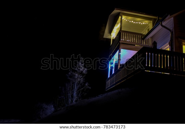 A brightly light house on a hill in snow and in darkness