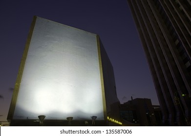 Brightly lit blank billboard stands out from the downtown area around at the early evening hours. Good as copy space for demonstrations etc.