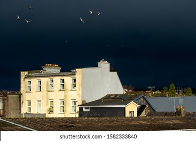 Brightly lit building against dramatic stormy dark sky as urban juxtaposition. contrast.