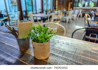 A brightly lit cafe with table and chairs with no customers